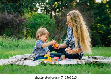 Pretty young blonde woman in  having fun in park on blanket with cute little son. Handsome mother playing with baby boy outdoors.