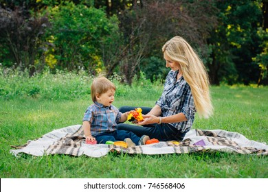 Pretty young blonde woman in  having fun in park on blanket with cute little son. Handsome mother with baby boy outdoors