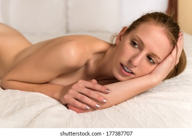 Pretty young blonde woman lying nude in bed