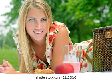 Pretty young blonde woman resting on elbows on picnic blanket - smiling