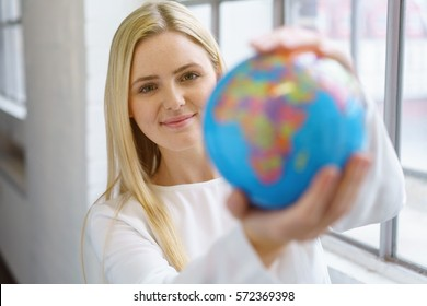 Pretty young blonde woman in white blouse looking at small globe in her hands blurred in the foreground
