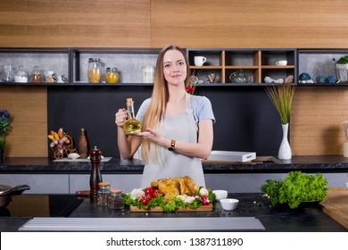 Pretty young blondie chef cooker preparing chicken or turkey in uniform with knife, spices, herbs, oil. Food, cooker concept