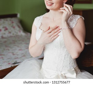 Pretty young Bride. Boudoir morning of the bride. Looking on her bouquet. Bride in boudoir dress. Bride's coiffure. Bride's coiffure. Young girl putting on earring