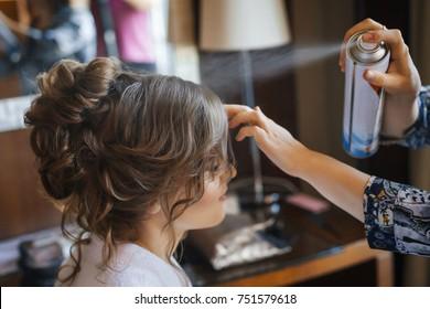 Hübsche junge Braut, die sich auf die Hochzeit am Morgen vorbereiten. Stylistische Frisur und Haarspray auf lockiges Haar