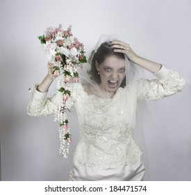 Pretty young bride screaming and holding bouquet with pink roses