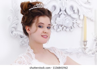 Pretty young bride in white dress poses near wall with molding and candle in studio