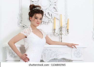 Pretty young bride in white dress poses near fireplace with candles in studio