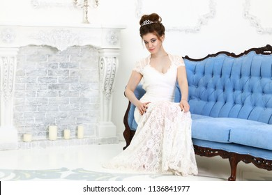Pretty young bride in white dress sits on blue baroque sofa in studio with fireplace