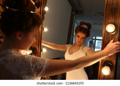 Pretty young bride in white dress looks in mirror with lamps in studio