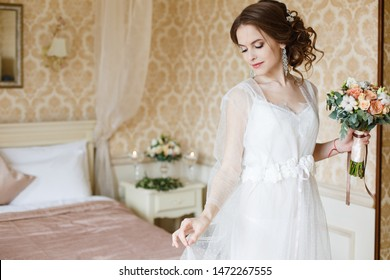 Pretty young Bride.Brown-haired woman with classic wedding hair-style. Boudoir morning of the bride. Taking a little candle in her hands