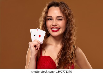 Pretty young brown-haired woman in red cocktail dress holding pair of aces and smiling