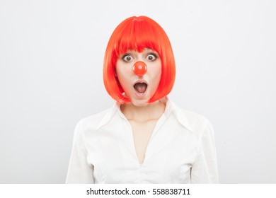 pretty young brunette caucasian woman with red nose and wig making a face surprised on white background