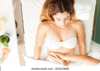 Pretty young brunette getting a lymphatic stomach massage from a therapist at a health clinic and spa, seen from above