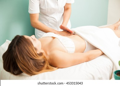 Pretty young brunette getting a lymphatic massage on her belly at a healthy and beauty spa clinic
