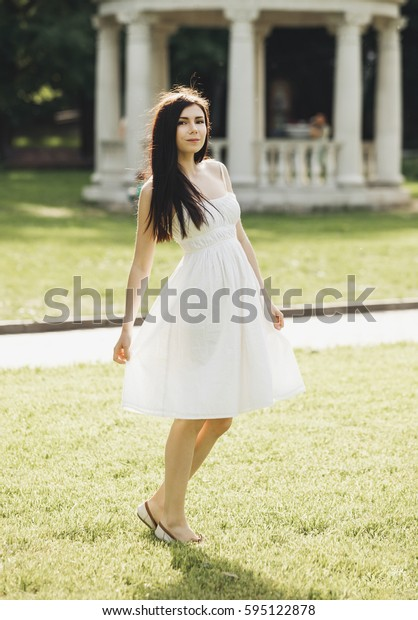 Pretty young brunette girl in light sundress enjoy good spring day in outdoor park.Warm season background.Young woman walk in blooming green park.Fashionable cute female model with long dark hair pose