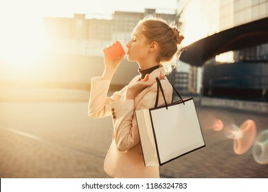 Pretty young brunette girl make selfie on the street. outdoor hipster portrait,happy face,sunglasses,smile,hot coffee, morning drinking, autumn atmosphere moods, shopping,with purchases from the store