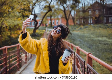 Pretty young brunette girl make selfie on the street. outdoor hipster portrait, happy face, sunglasses, smile, hot coffee, morning drinking, autumn atmosphere moods