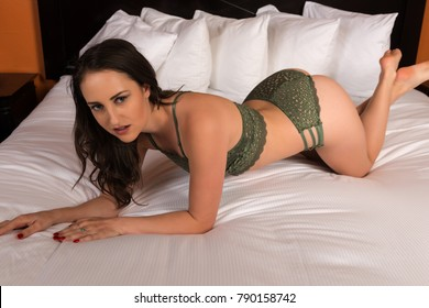 Pretty young brunette in green lingerie