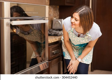 Pretty young brunette looking into an oven and checking if the cake is already baked and ready