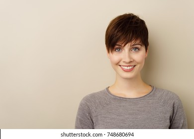 Pretty young brunette with short hair looking at the camera with a bright friendly smile over white with copy space