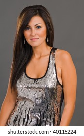 Pretty young brunette in a silver and black sequined dress