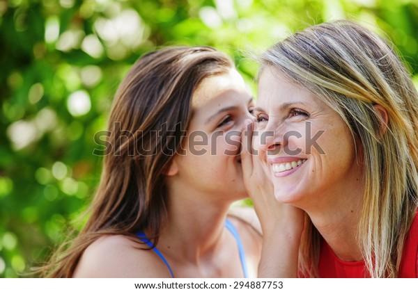 Schöne junge Brunette flüsterend im Ohr ihrer Mutter