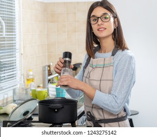 a pretty young brunette woman cooking in the kitchen