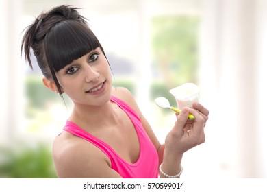 pretty young brunette woman eats a yogurt