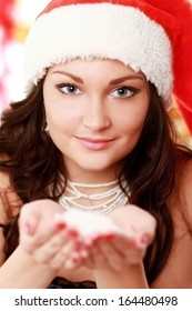 Pretty young brunette woman on santa hat with snow her hands