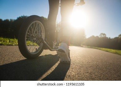 Pretty young brunette woman riding on a push sport on a bike path during lovely summer sunset (color toned image)