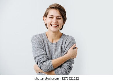 Pretty young brunette woman with short hair with a bright friendly open smile in u neck grey sweater over white background with copy space. She looks at camera, hugging herself. Laughing.