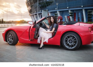 Amazing Pretty Young Brunette Woman Sitting At Luxury Red Cabriolet Car At The  Sunset