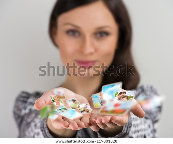 Pretty young brunette woman smiling with hands cupped together, sharing her photo and video files in social media resources. Virtual interface of future concept.