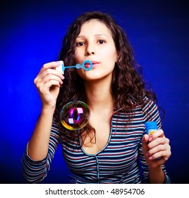 pretty young brunette woman with soap bubbles against blue background