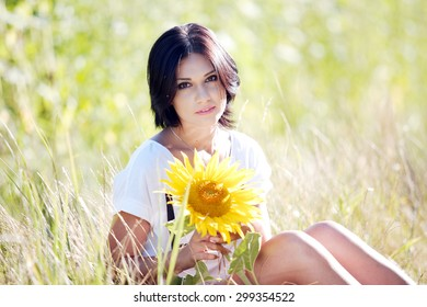 Pretty young brunette woman in a sunflower field holding a sunflower.