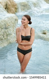 Pretty young brunette woman taking a bath in the natural thermal waters of spa, Saturnia Italy