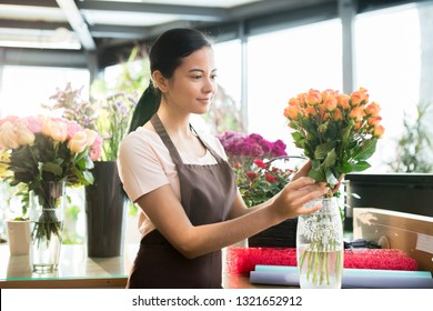 Pretty young brunette woman in workwear putting fresh orange roses into vase while sorting flowera in florist shop