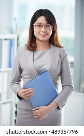 Pretty young business lady with folder of documents