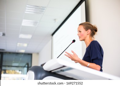 Pretty young business woman giving a presentation in a conference/meeting setting (shallow DOF; color toned image)