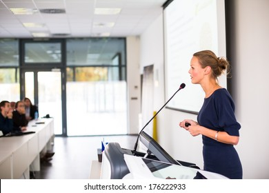 Pretty, young business woman giving a presentation in a conference/meeting setting (shallow DOF; color toned image)