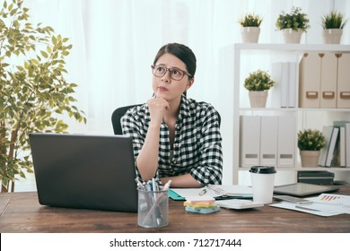 pretty young business woman worker working at home and having difficulty problem looking at air daydreaming to think solution.