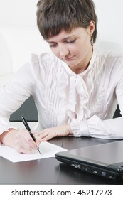 Pretty young businesswoman sitting at desk and writing on blank paper