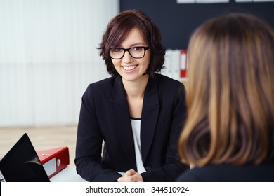 Pretty Young Businesswoman Smiling at the Camera While Talking with her Co-worker During a One-on-One Meeting inside the Office.