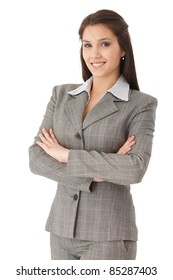 Pretty young businesswoman standing arms crossed, smiling, looking at camera.?