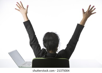 Pretty young businesswoman stretching while sitting at her desk