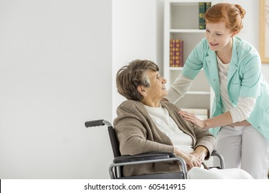 Pretty young caregiver helping elderly disabled woman in nursing home