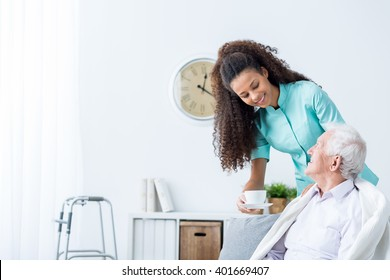Pretty young caregiver serving afternoon cup of tea to older happy man