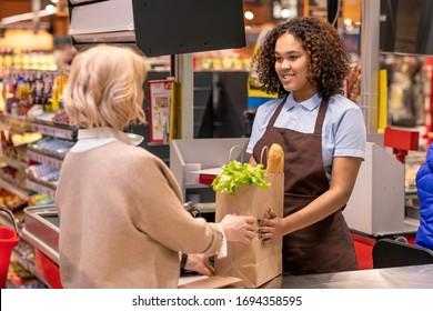Jolie jeune caissière donnant des cartons féminins matures avec du pain et de l'épicerie fraîche tout en étant debout dans une caisse au supermarché
