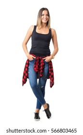 Pretty young casual woman with shirt tied around waist and hands in pockets smiling. Full body length portrait isolated over white studio background.