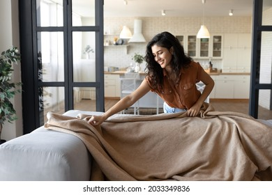 Pretty young Caucasian lady putting warm plaid on comfy sofa, getting ready for autumn or winter season at home, copy space. Trendy house decor, interior design concept